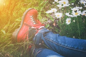 person wearing hiking boot surrounded by spring flowers
