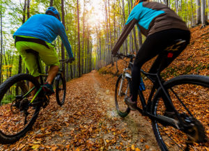 Mountain biking in autumn landscape forest. Man and woman cycling MTB flow uphill trail.